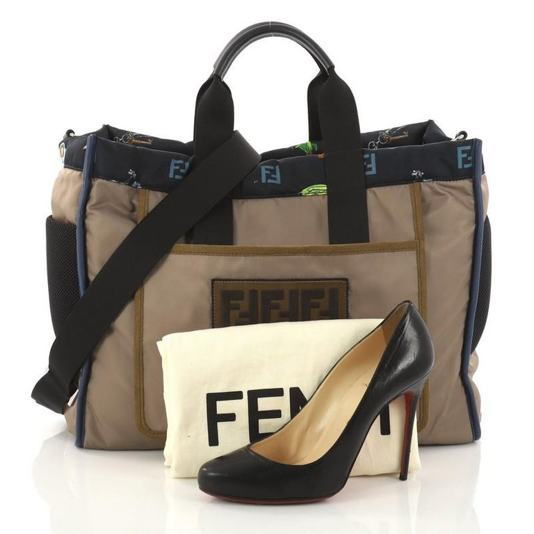 This authentic Fendi Reversible Tote Printed Nylon Large is perfect for everyday casual looks. Crafted in army green nylon, this chic bag features dual flat handles, large patch pocket and the two side pockets in technical mesh which are functional