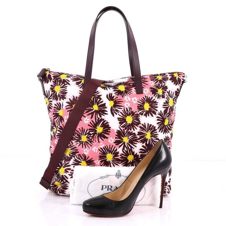 This authentic Prada Convertible Tote Printed Tessuto With Saffiano Large is an eye-catching piece perfect for modern fashionistas. Crafted from maroon and pink printed tessuto with maroon Saffiano leather, this tote features a stunning floral print