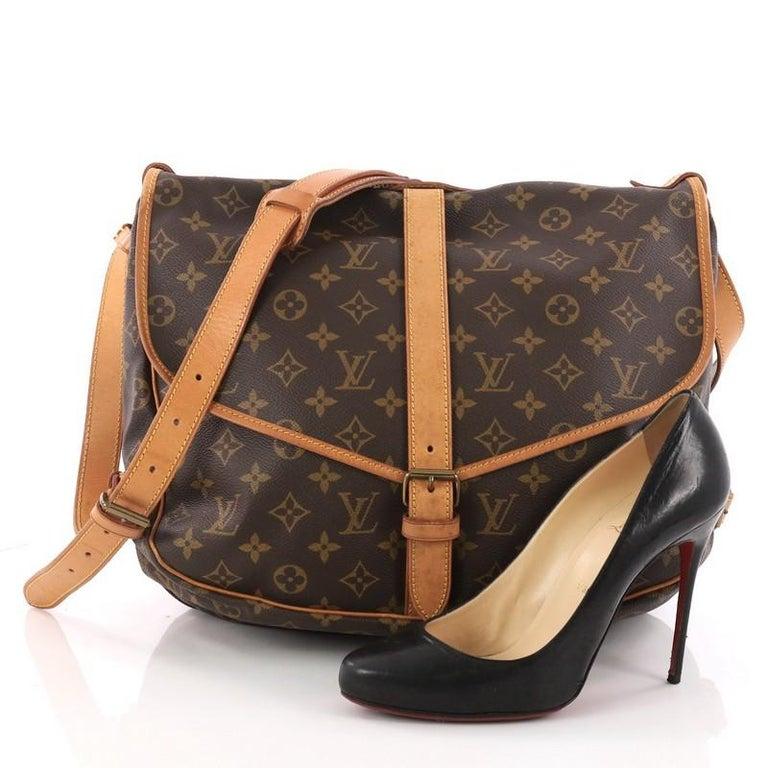This authentic Louis Vuitton Saumur Handbag Monogram Canvas MM showcases  the brand s reinterpretation of the classic 58d9ad8c79ee5