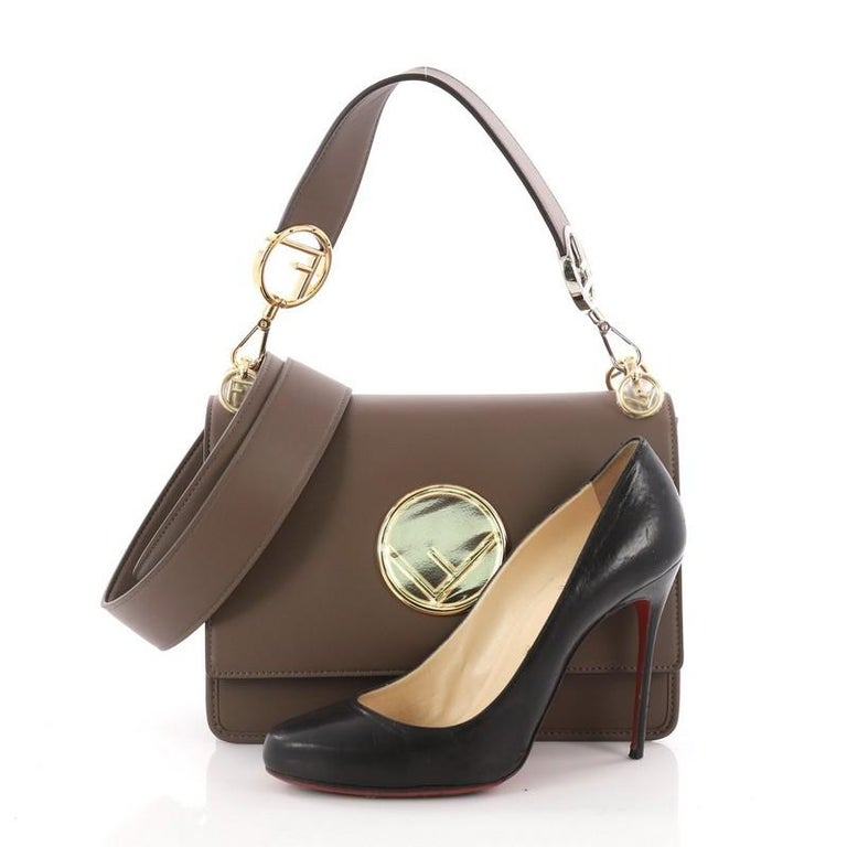 This authentic Fendi Kan I F Shoulder Bag Leather Medium is a uniquely designed bag perfect for the stylish fashionista. Crafted from brown leather, this bag features a detachable flat leather top handle, Fendi logo, detachable shoulder strap, and