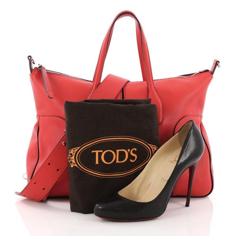 This authentic Tod's Piccolo Tote Leather Medium showcases the brand's minimalist, modern casual style. Crafted from red leather, this versatile satchel features dual-leather handles, and silver-tone hardware accents. Its top zip closure opens to a