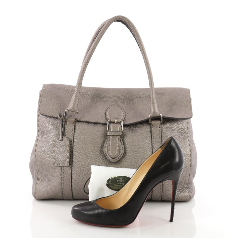 This authentic Fendi Selleria Linda Satchel Pebbled Leather Large is a classic stylish bag perfect for daily or work excursions. Constructed from pewter pebbled leather, this stylish satchel features rolled leather handles, hand stitched saddle top