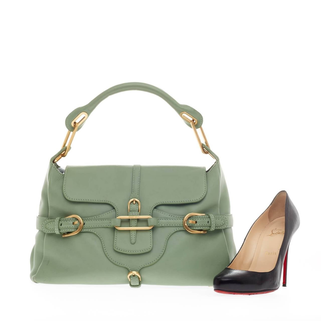 This authentic Jimmy Choo Tulita Shoulder Bag Leather is a stylish hobo perfect for a modern woman. Crafted from beautiful mint green smooth leather, this understated bag features a single rolled top handle, buckle strap details, protective base