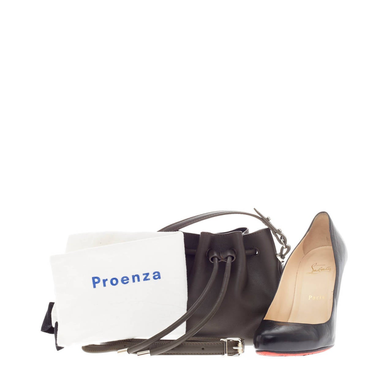 This authentic Proenza Schouler Bucket Bag Leather Tiny showcases a miniature style perfect for a care free on-the-go woman. Crafted in rich dark brown calfskin leather, this petite minimalist bucket bag features silver-tone hardware accents and a