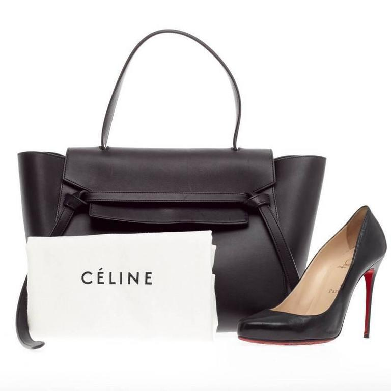 This authentic Celine Belt Bag Calfskin Medium is sure to make a statement. Crafted from navy blue calfskin leather, the bold and beautiful bag features expanded wings, looped single top handle, top flap slide closure, zipper pocket at the back for