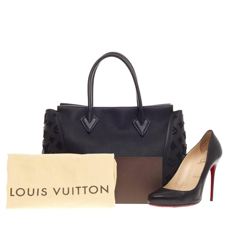 This authentic  Louis Vuitton W Tote Veau Cachemire PM is a collector's dreams with a fresh and youthful design made for the modern woman. Crafted black veau cachemire leather, this luxurious and elegant handbag features dual-rolled handles,