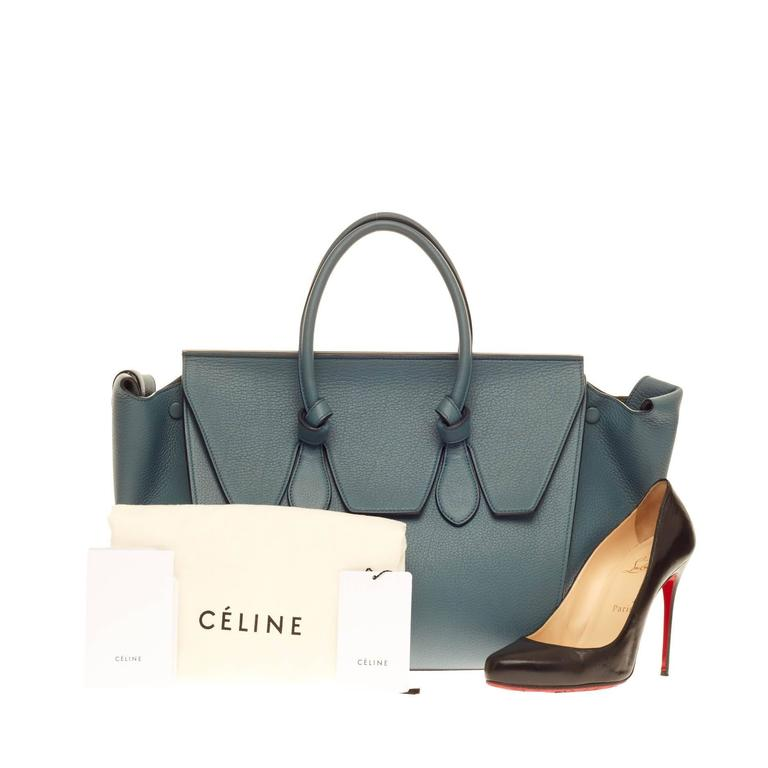 This authentic Celine Tie Knot Tote Grainy Leather Large presented in the brand's Spring/Summer 2014 Collection is an absolute must-have for serious fashionistas. Crafted from denim blue grainy calfskin leather, this boxy, chic tote features
