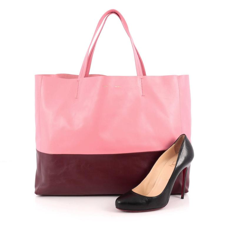 This authentic Celine Horizontal Bi-Cabas Tote Leather Large is the perfect oversized easy companion to fit all your essentials and more. Crafted in bicolor pink and burgundy leather in a minimalist design, this no-fuss tote features dual flat
