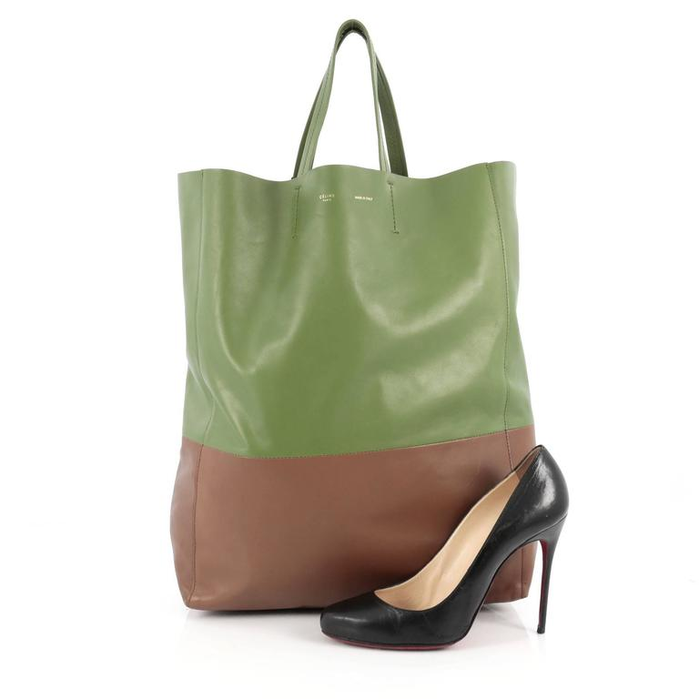 This authentic Celine Vertical Bi-Cabas Tote Leather Large is a perfect everyday accessory for the woman on-the-go. Crafted in minimalistic bi-color green and brown leather, this no-fuss tall tote features slim top handles and gold-tone hardware
