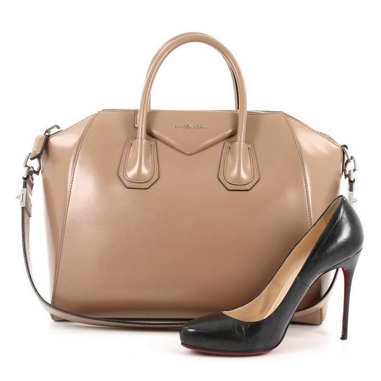 This authentic Givenchy Antigona Bag Glazed Leather Medium combines style and functionality all-in-one. Crafted from sleek, light brown leather, this structured handle bag features dual-rolled leather handle, brand's signature envelope flap detail