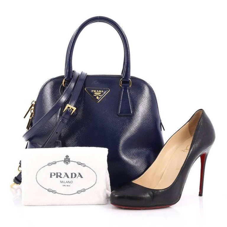 This authentic Prada Zip Around Convertible Dome Satchel Vernice Saffiano Leather North South is the perfect companion for an everyday stroll. Crafted from dark blue vernice saffiano leather, this chic dome-shaped bag features dual-rolled handles,