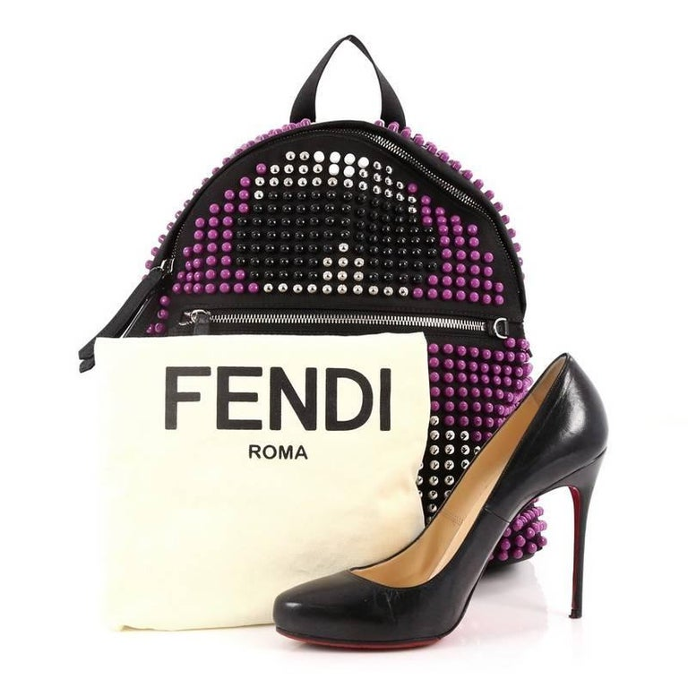 This authentic Fendi Karlito Backpack Studded Nylon is an eye catching, luxurious, playful style made for on-the-go fashionistas. Crafted from purple, black and white studded nylon, this backpack features adjustable canvas straps, exterior front zip