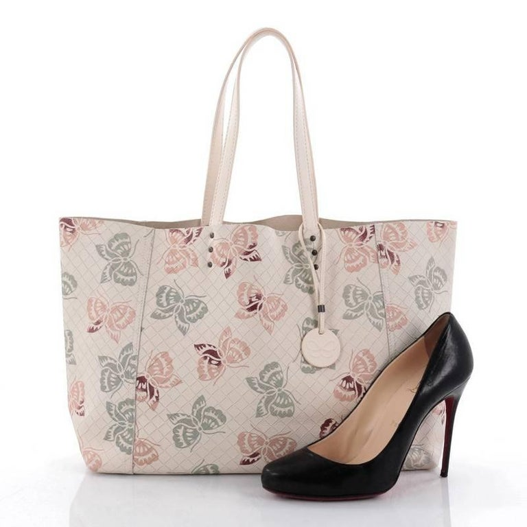 This authentic Bottega Veneta Tote Butterfly Embossed Intrecciomirage Intarsio Leather Large is a classic styled Bottega bag perfect for your everyday use. Crafted from beige intrecciomirage intarsio leather with embossed impressions across the bag