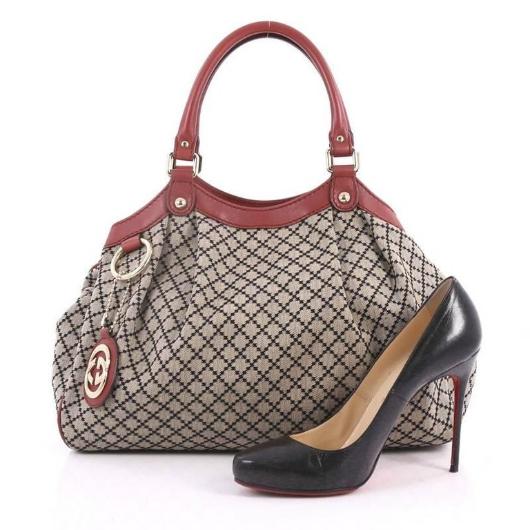 This authentic Gucci Sukey Tote Diamante Canvas Medium is sophisticated in design is modernly chic perfect for casual excursions. Crafted in signature beige diamante canvas with leather trims, this soft structured bag features dual-rolled handles,