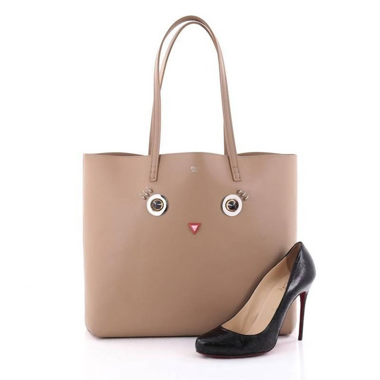 This authentic Fendi Faces Roll Tote Embellished Leather Large features a playfully striking detail elaborating the elegantly decadent spirit of the brand. Crafted from light brown leather with eyes and mouth embellishments, this chic tote features