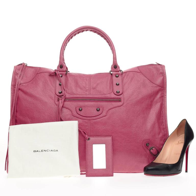 This authentic Balenciaga Weekender Classic Studs Leather is a stylish and fun accessory made for light travels and weekend getaways. Constructed from beautiful cyclamen pink leather, this oversized, lightweight carryall features braided woven