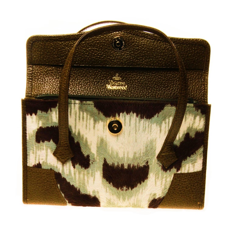 This VIVIENNE WESTWOOD printed pony hair top handle handbag is a unique and clever cross between a hand bag and a wallet.  Beautifully crafted interior in olive green leather, features multiple compartments and card holders. A perfect travel