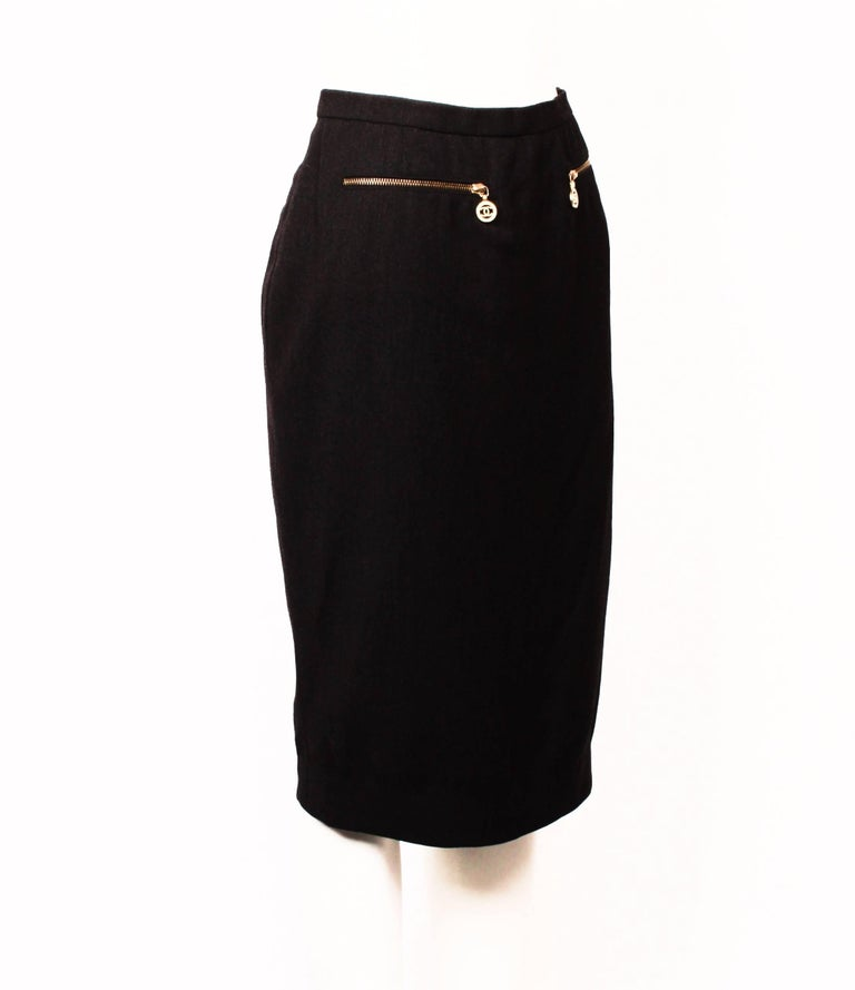 Gorgeous Chanel Boutique fitted pencil skirt in dark charcoal grey. Features decorative gold zipper pockets with iconic Chanel CC logo pulls.  The skirt is just below knee length and is fully lined. Back invisible zipper and hook and eye