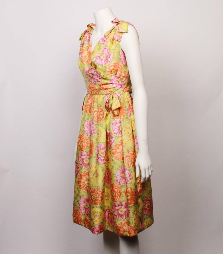 Early 1960s Christian Dior demi– couture new look floral party dress in 100% silk multi coloured floral fabric in hues of fresh citrus green, yellow, orange and pink. Cross over front and back bodice with a slightly gathered skirt.  Features