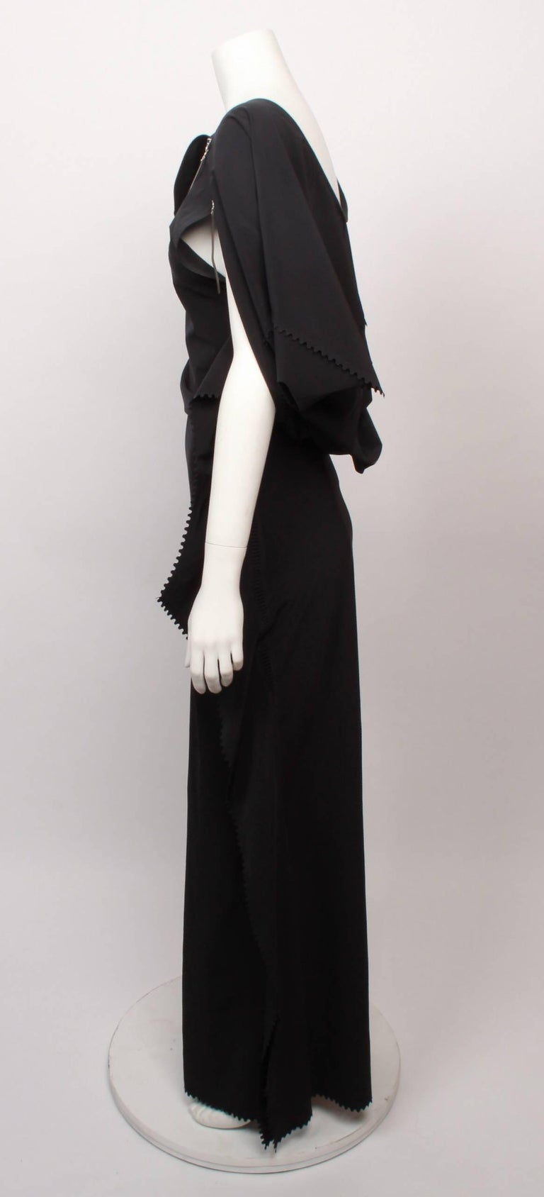 Issey Miyake long black art wear maxi dress  with hi-tech feature laser cut panels and edging, and zippers that unzip to create the neckline and armholes. Zippers have decorative opaque white rubber toggles.  Back bodice is draped to the waist and