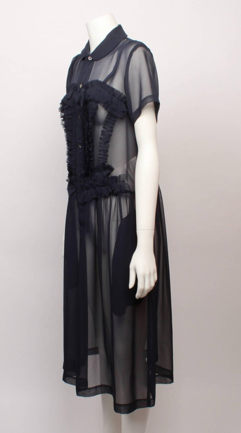 Comme des Garcons Sheer navy silk chiffon frill dress features soft tuxedo frills with decorative bow.  Frills also run horizontally above the bust line to create a cute sweetheart shape.   Dress has a peter pan collar, button through front placket