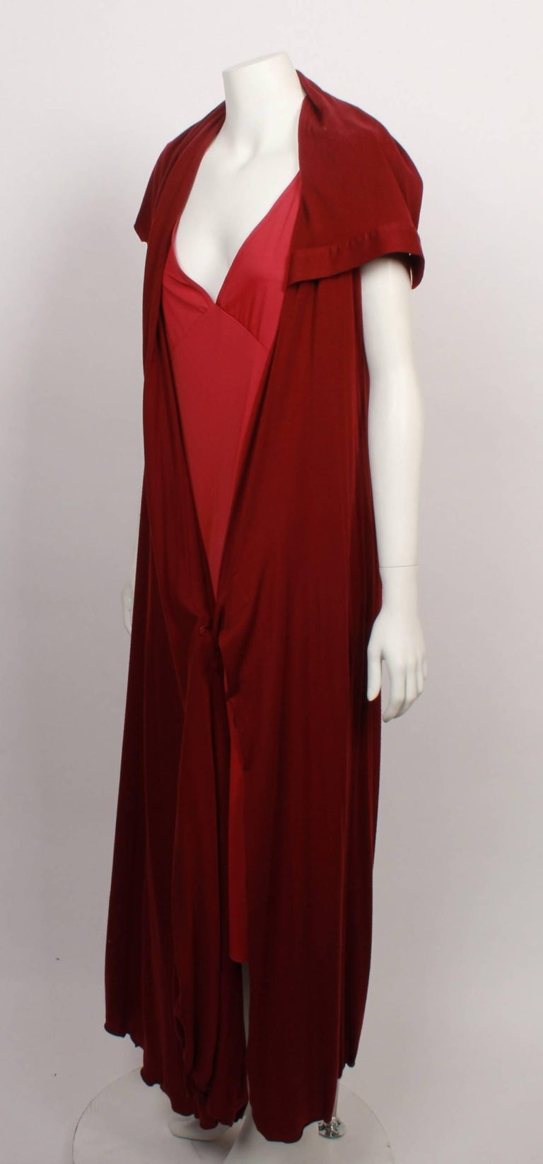 Issey Miyake timeless long stretch jersey raspberry coloured wrap dress with matching under slip. Features asymmetrical wide shawl collar, short extended sleeve and feminine flared hemline. Has a flaw in dress. Made in Japan.