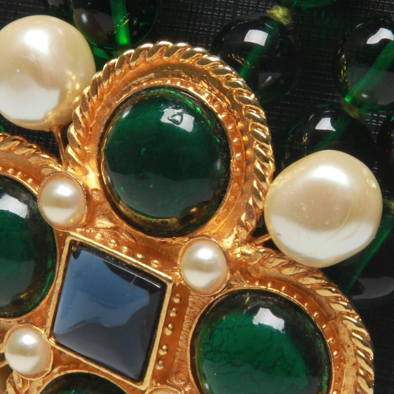 A pristine vintage style Chanel necklace with a gripoix brooch features emerald and blue poured glass detail with pearl throughout the outside.  Fastener: Pins at the back.  Featuring x4 green giproix stones, x4 pearl with blue stone.  Highly