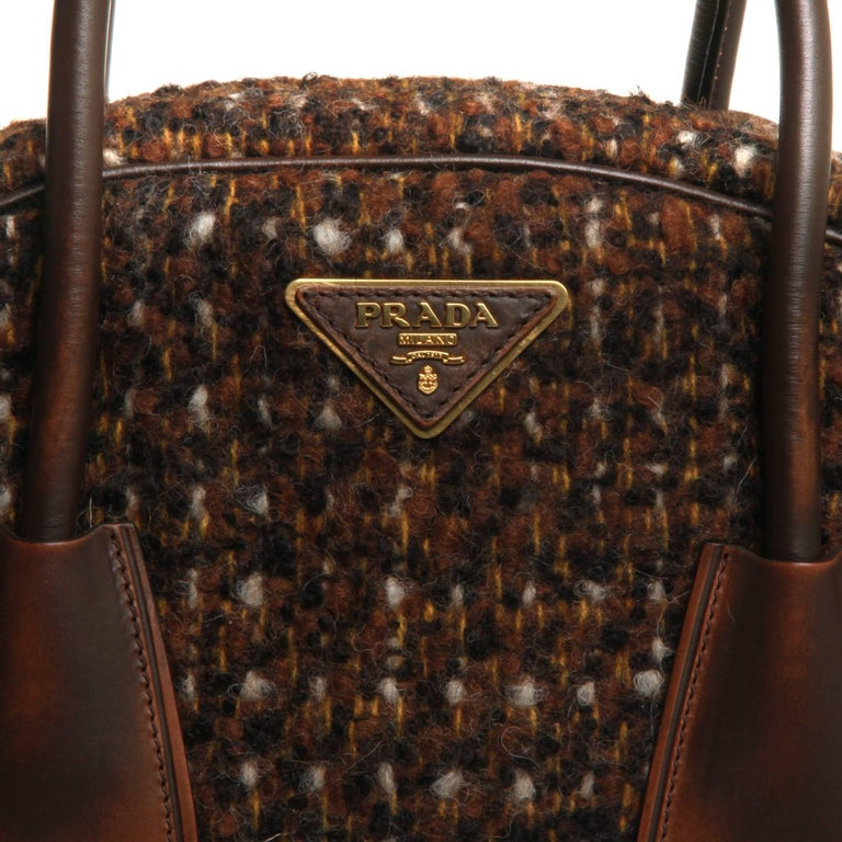 Brown and multicolor Tessuto wool tweed Prada Tessuto Wool Tweed Vitello Bowler Bag with gold-tone hardware, brown leather trim, logo at exterior, dual rolled top handles, dual interior pockets; one with zip closure and zip closure at top.
