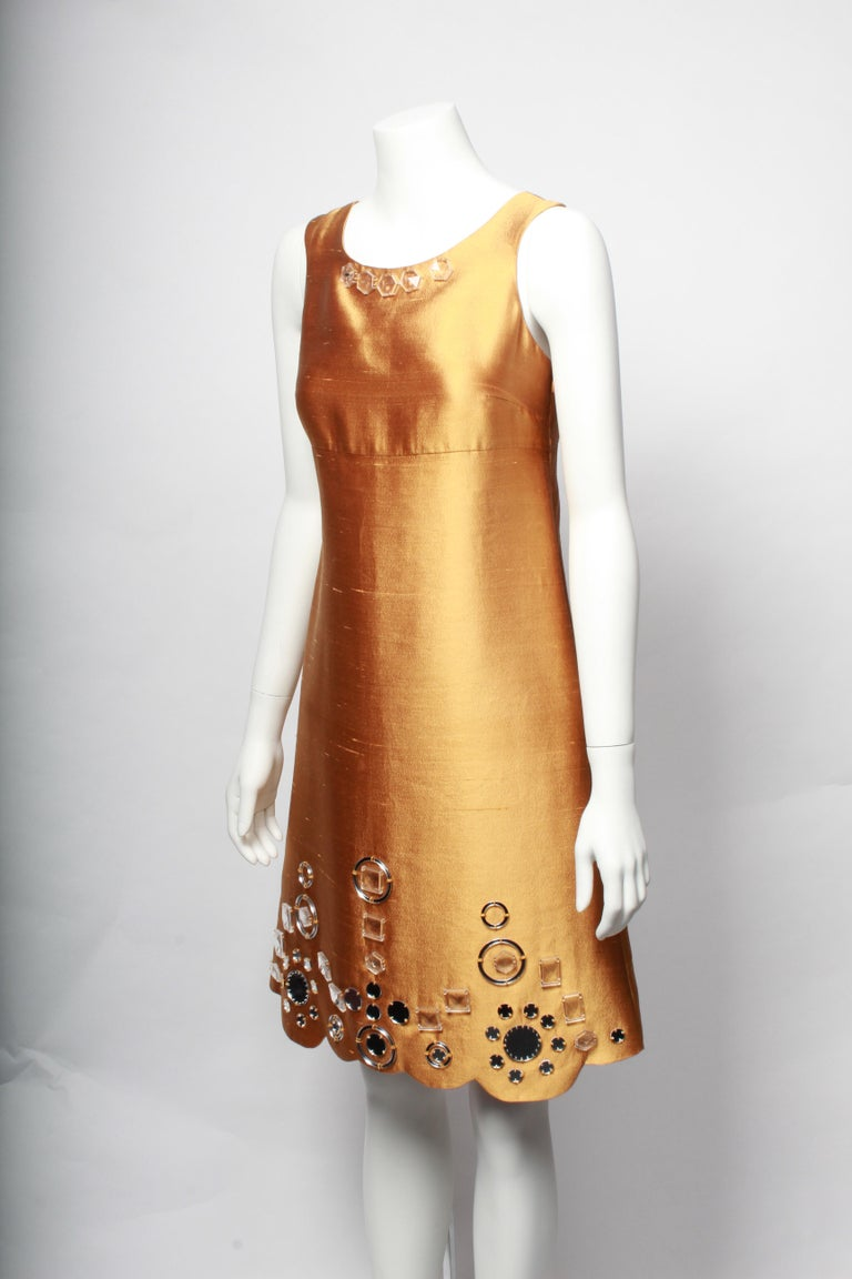 Gorgeous Miu Miu Gold Shift Dress. The dress is cut in a flattering A-line shape from under the breast. Made in wonderful gold silk, this dress features patterned mirror embellishments and is finished with a scalloped hem. An excellent party dress