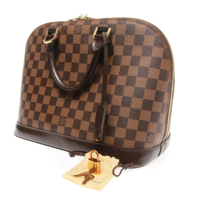e973d2d7062e The most structured of the iconic LOUIS VUITTON handbags. Featuring a  leather key clochette