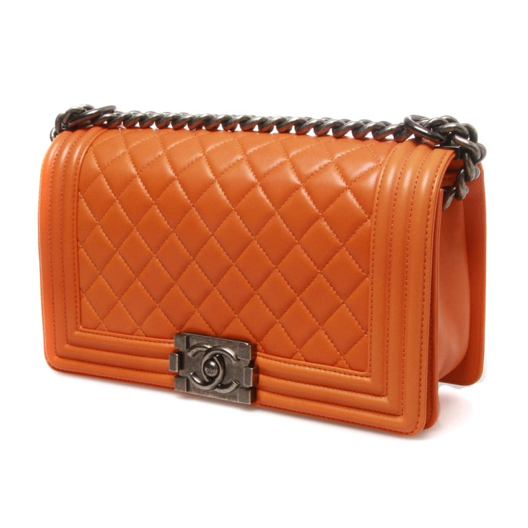 This collectable Chanel  Lambskin Quilted Medium Boy Flap Orange.  This chic shoulder bag is crafted of diamond quilted luxurious lambskin leather with a linear quilted border in orange. The bag features a ruthenium chain link shoulder strap with a