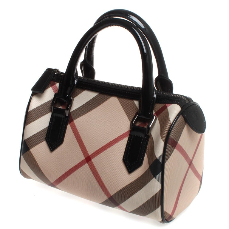 We guarantee this is an authentic Burberry Nova Check Small Chester Bowling Bag Black. This stylish tote is finely crafted of classic black, white, red and beige Nova check coated canvas. The bag features black rolled patent leather top handles and