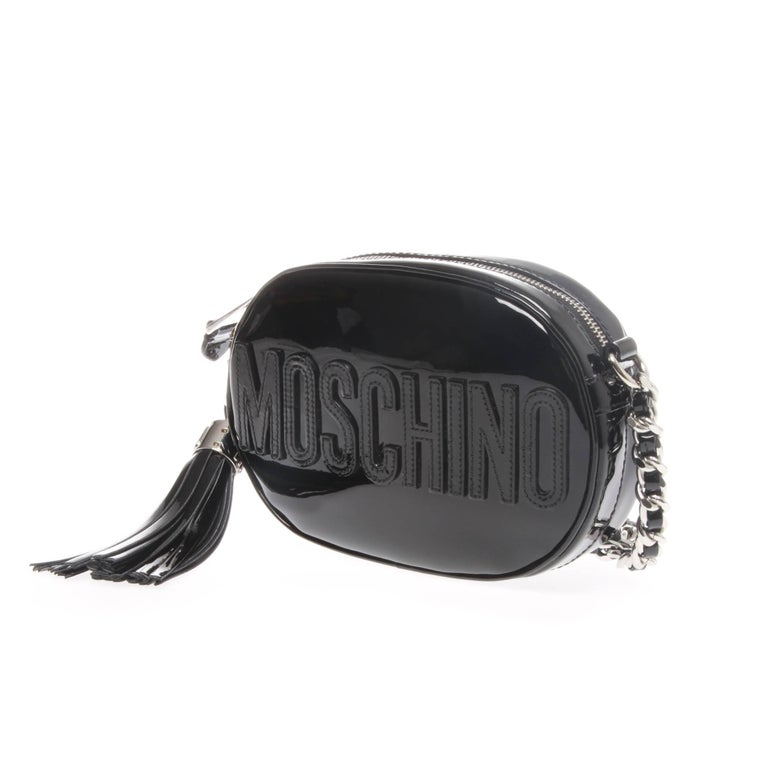 Moschino oval logo cross-body bag in black patent leather. MOSCHINO applique to front side is the bags main design feature, as well as a removable tassel bag charm in matching red patent leather that is also threaded through the chain shoulder