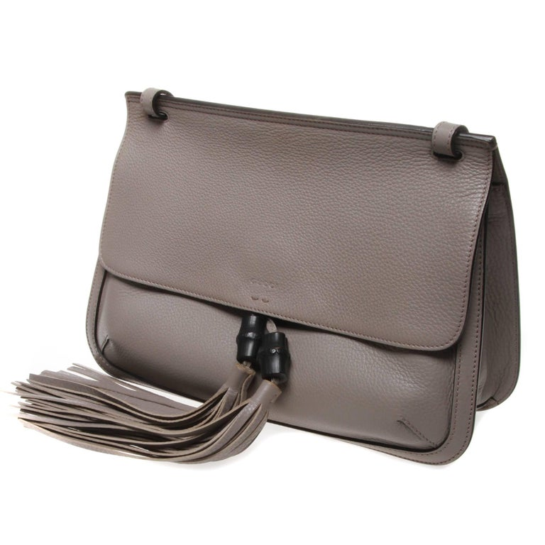 Gucci Bamboo Daily leather flap shoulder bag in light grey. This bag features a main compartment with two open pockets and one zip pocket sewn into the tone-on-tone baiadera cotton-linen lining, an open front pocket outside the main compartment and