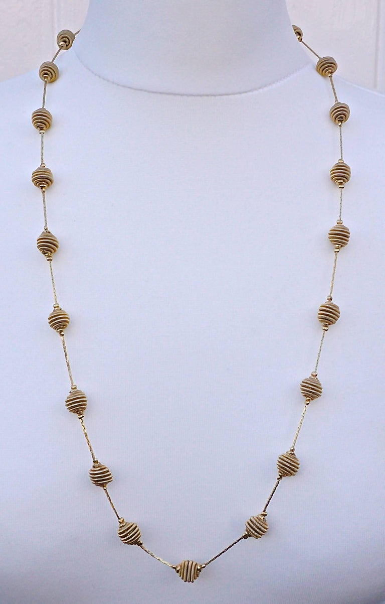 Fabulous Monet gold tone necklace with spiral balls joined together with shiny linked chain. It has the Monet hang tag. Length 76.5cm, 30 inches, and the spiral balls are diameter 1cm, .39 inch. This Monet design has been reinvented and is available