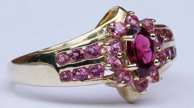 STS Jewels Inc. quality  14K gold ring featuring a faceted deep pink natural tourmaline, and twenty two light pink gemstones. Twelve of the faceted light pink stones are channel set, six to each side, and ten are in a cluster around the