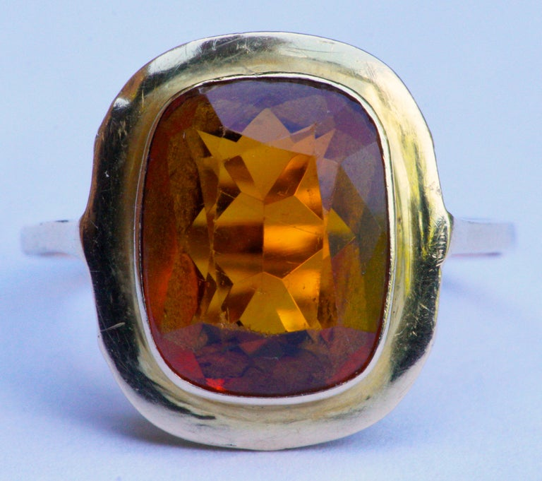 18ct gold ring set with a faceted citrine, ring size UK N, US 6 1/2. It is unmarked, but tests as 18ct gold. The band is of slightly lower grade gold, and tests as 14ct. Circa 1950s. The citrine is 1.15cm, .45 inch, by 9mm, .35 inch. The setting