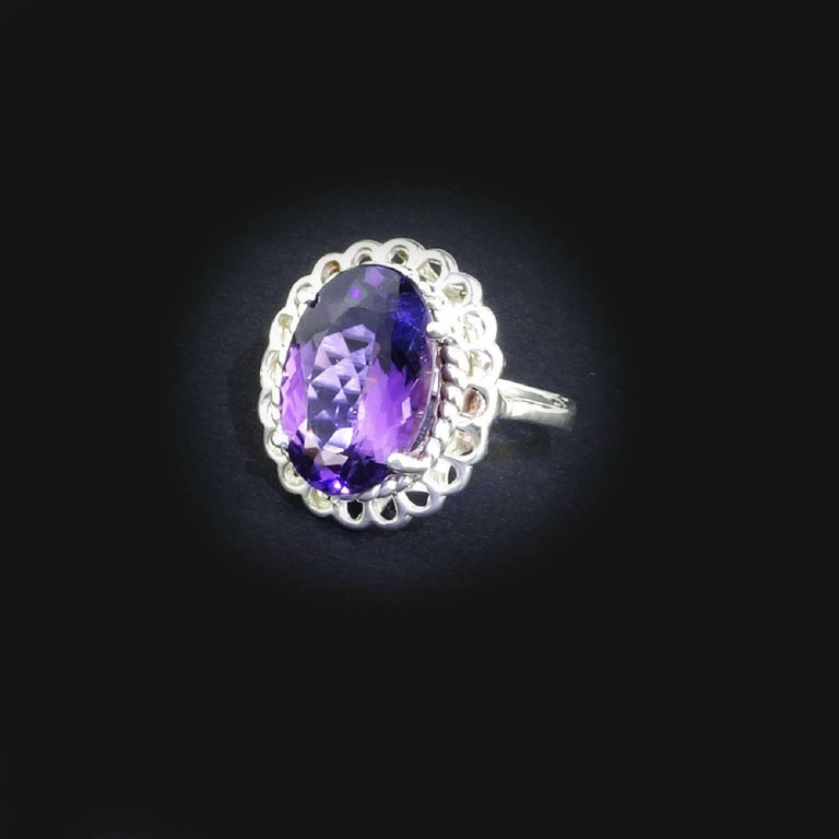 Custom made, sparkling oval Amethyst Ring.  This lively Amethyst has delightful pink flashes and is set in a lovely detailed high basket setting of Rhodium over Sterling Silver Ring.  This 4.62 carat Amethyst comes from one of our favorite suppliers