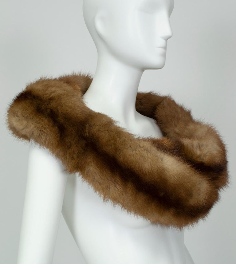 As timeless as a set of pearls, fur shoulder cowls convey ladylike elegance and remain essential-wearing with strapless dresses. The braided feature on this piece permits a variety of uses: clasp around shoulders as a wrap, tuck one end through