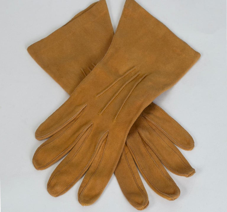 Your go-to glove for work, dress and play, guaranteed to be in your handbag throughout the winter. Buttery and supple, in the perfect shade of Hermès saddle tan.  Saddle suede wrist-length dress gloves with fourchettes, quirks and three points at