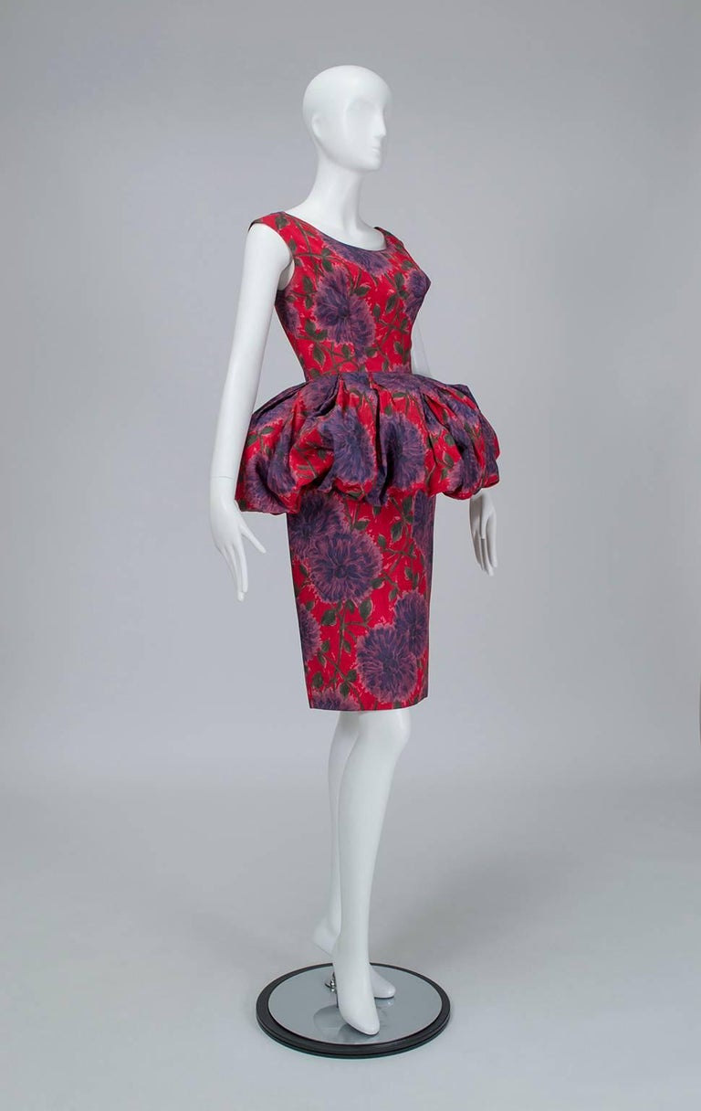 Less a peplum and more a Renaissance-era farthingale, this dress's midsection uses an optical illusion to slim the waist and hips by comparison. Entrance- AND exit-making.  Vintage sleeveless sheath dress with wide scooping neckline and front and