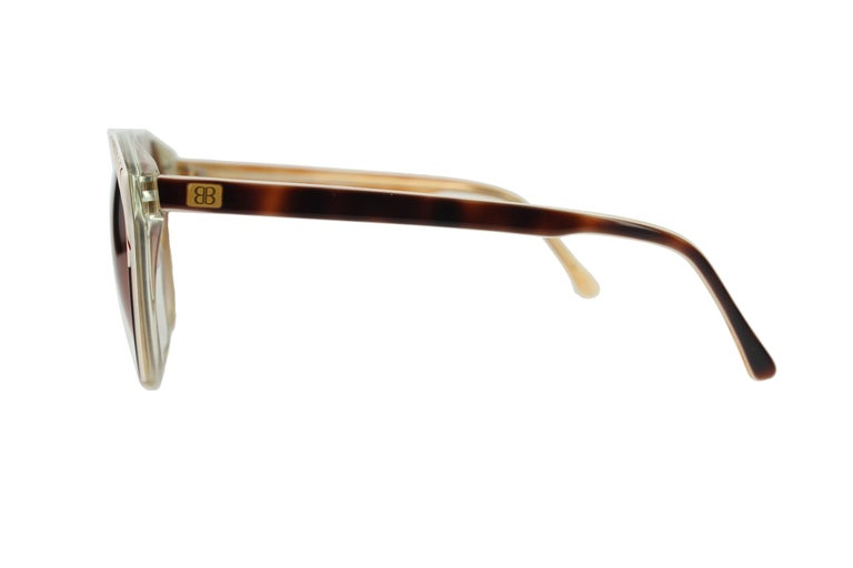 "Delicate sunglasses hand made by the renowned Balenciaga brand. Its frame in rounded shape and soft color, made in acetate, has a casual-chic and ""vintage"" style that is very attractive. Lenses are gradient brown.  Measurements - Distance"