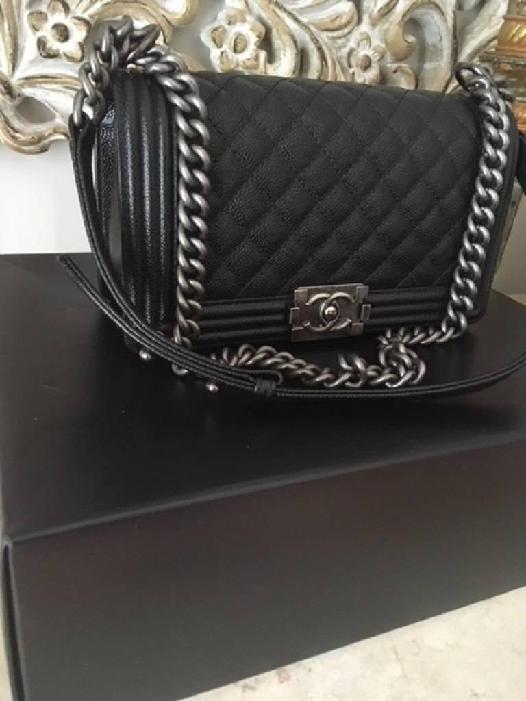 This gorgeous boy bag features the popular caviar leather with the silver tone hardware. The bag is the medium size and has 1 internal pocket . On the outside is the CHANEL CC lock closure. The handles can be worn as a single or as a double.  BAG IS