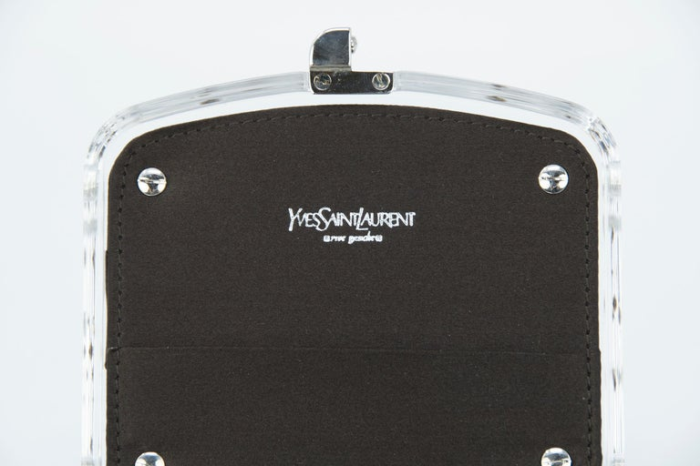 Designed by Tom Ford for Yves Saint Laurent for the Fall 2003 collection is a great mini clutch. This delicate lucite minaudière, lined in black with silver closure and rhinestone details on both the front and back.   Condition: Pristine  Dimensions