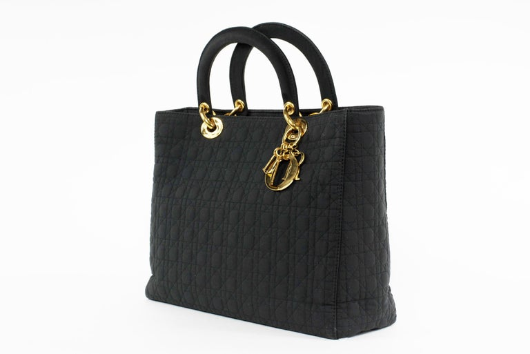 Classic Lady Dior Cannage quilted handbag in nylon with tonal topstitching.  Features gold logo charm hardware and top handles.  Condition: New  Approximate Measurements:   H 9.5 in. x W 12.5 in. x D 4.5 in.  H 24.13 cm x W 31.75 cm x D 11.43 cm