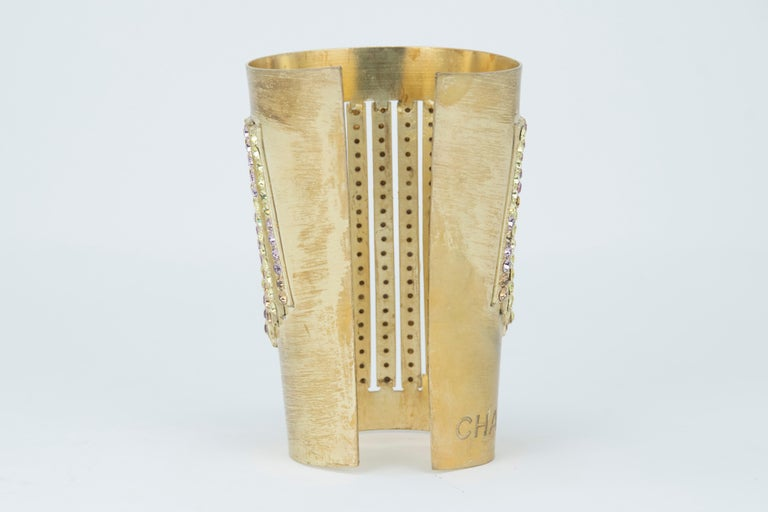 This Chanel cuff makes for an incredible statement piece.  Gold with rows of consecutive multicolored rhinestones.  Chanel engraved into the side of the gold.  Perfect for a more dressed up look or to pair with a button down and jeans.  Condition: