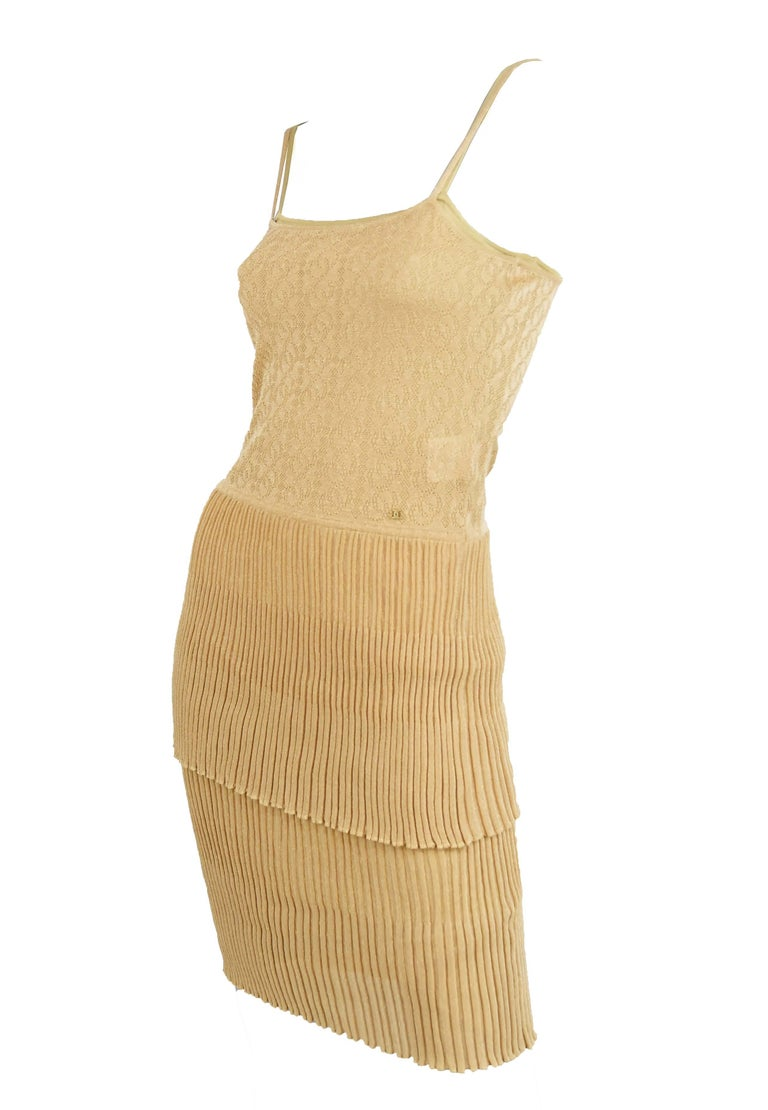 Chanel gold knit spaghetti strap dress with two tiers of beautiful pleating.  Jeweled Chanel logo sewn into the bodice.  Size: FR 36  Condition: Pristine condition  Composition: 80% rayon, 20% polyester / (lining) 100% rayon  Care: Dry clean