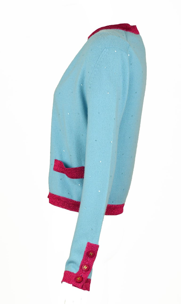 Beautiful light blue cashmere sweater set with clear sequins scattered over the fabric.  Pink metallic trim gives this look a modern feel.  Featured pink buttons with gold CC logo.  Size: FR 38  Condition: Pristine  Made in France