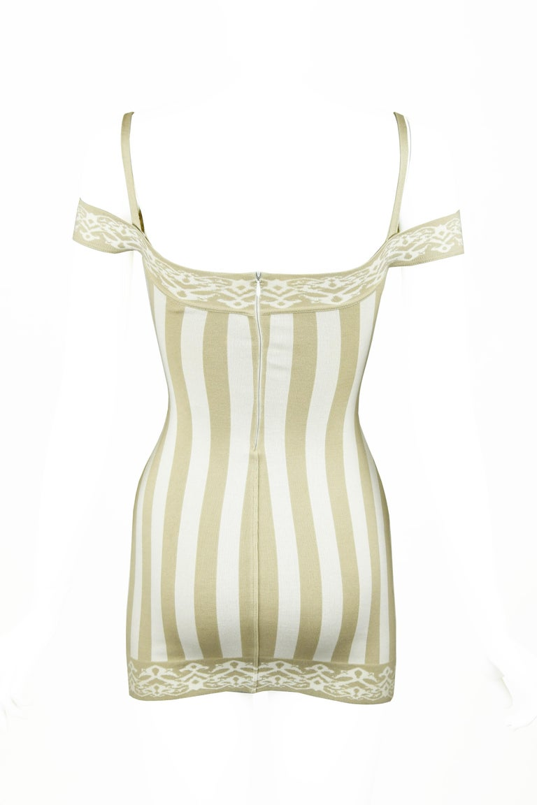 Iconic Azzedine Alaia piece from the 1990s.  Do not miss out on the opportunity to own a piece from one of his very famous collections.  Off white and bone striped knit mini dress made out of a cotton blend.  Features spaghetti and off the shoulder