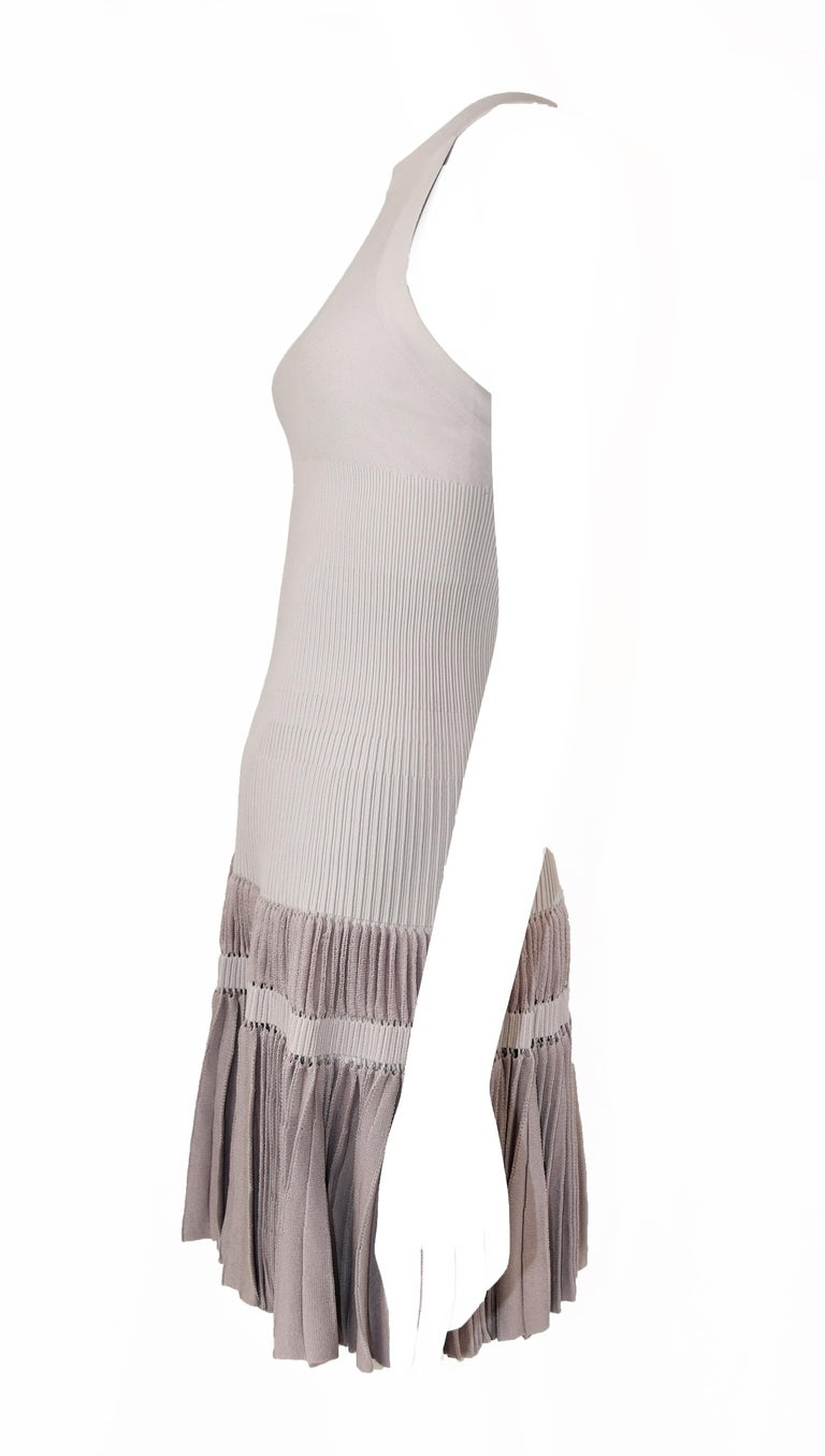 Incredible pale lilac/gray knit racer back dress.  Fitted throughout the bodice and flirty pleating at hem.  Classic Alaia piece.  Size: Size FR 40  Condition: Excellent condition  Composition: 45% silk, 45% viscose, 10% rayon  Care: Dry clean